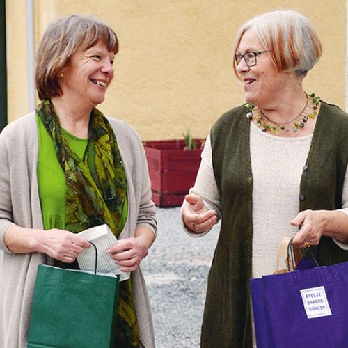 Butiker i Kvarteret Bryggeriet. Två kvinnor med shoppingkassar pratar och skrattar.